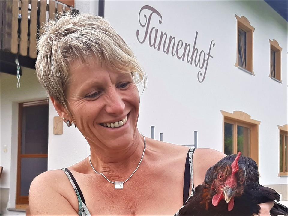 Christina Müller mit einem Hahn im Arm
