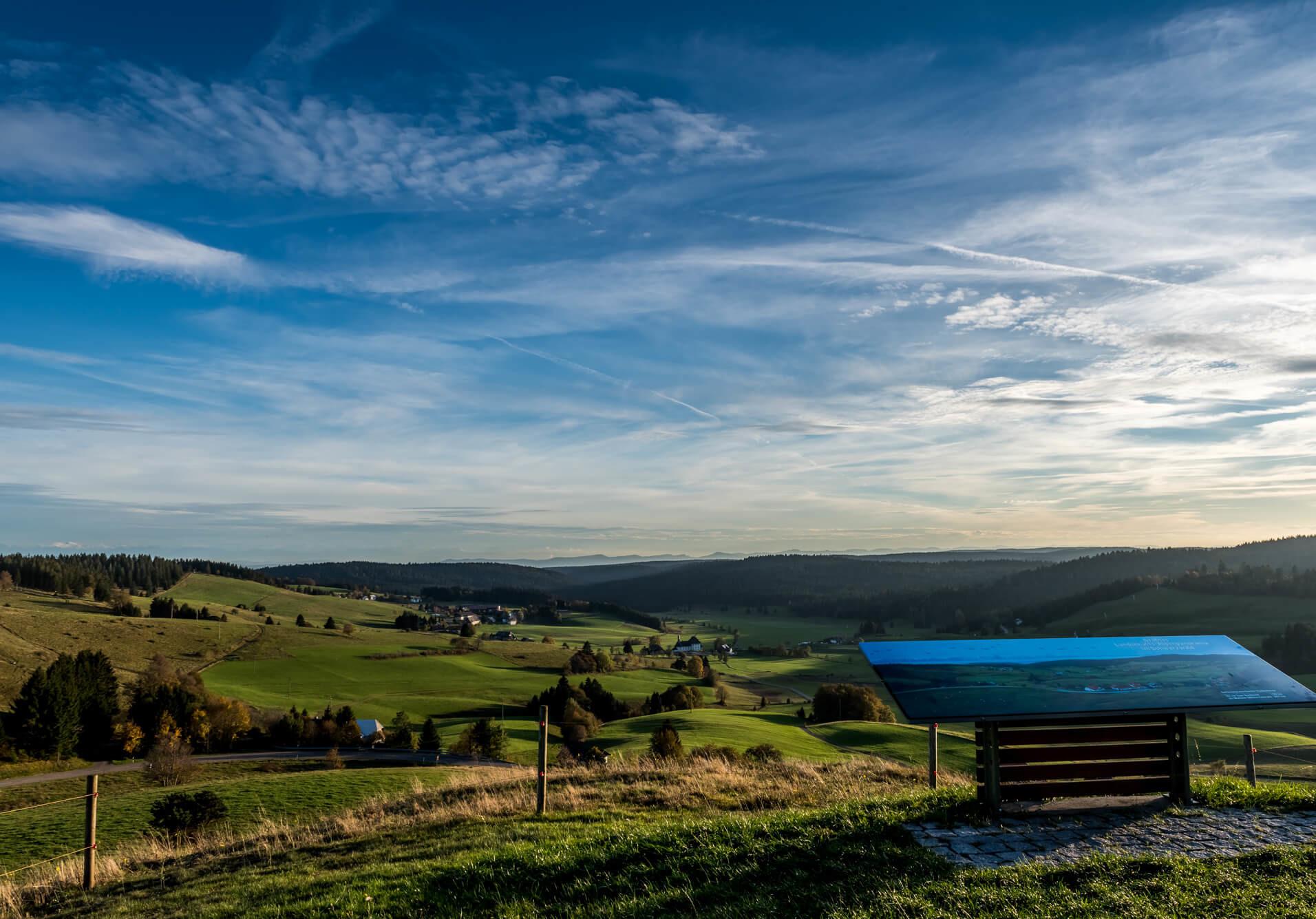 Auf dem Ibacher Panoramaweg mit Panoramatafel, Feldern und einem wolkenreichen Horizont