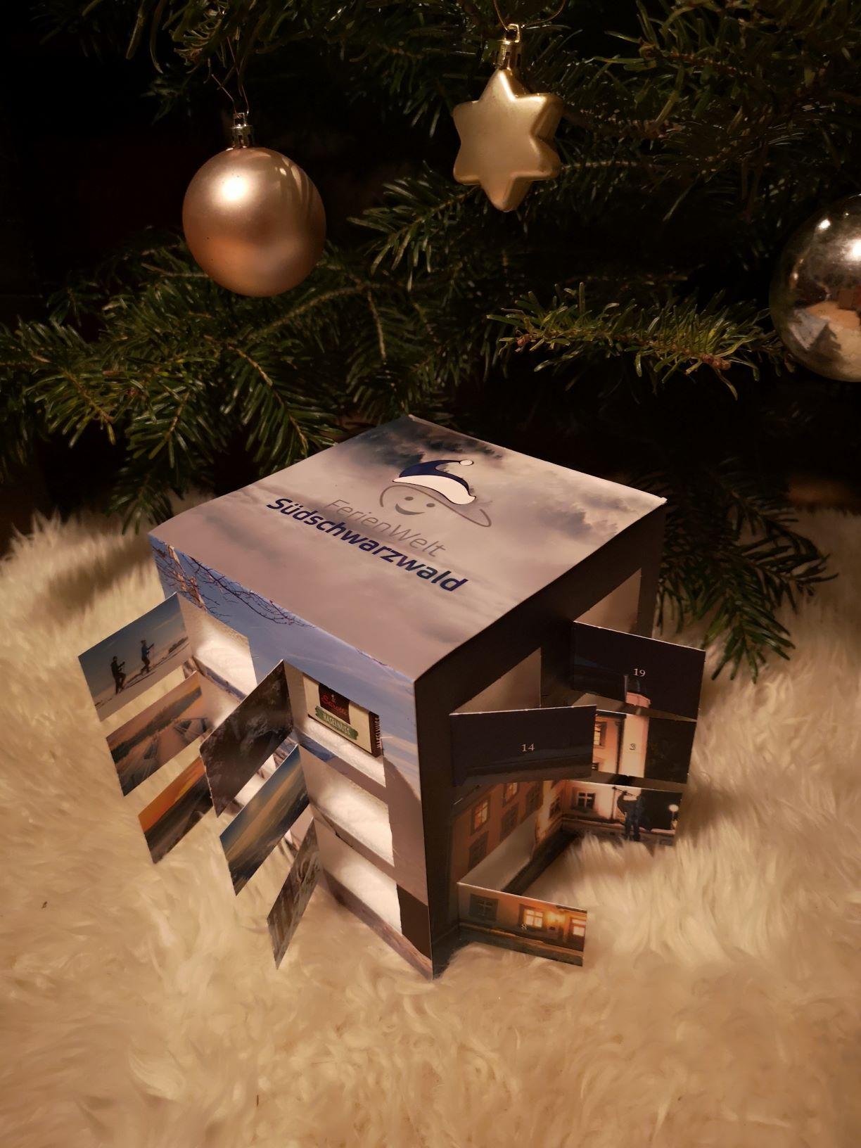 Adventskalender der Ferienwelt vor weihnachtlich geschmückten Tannenbaum