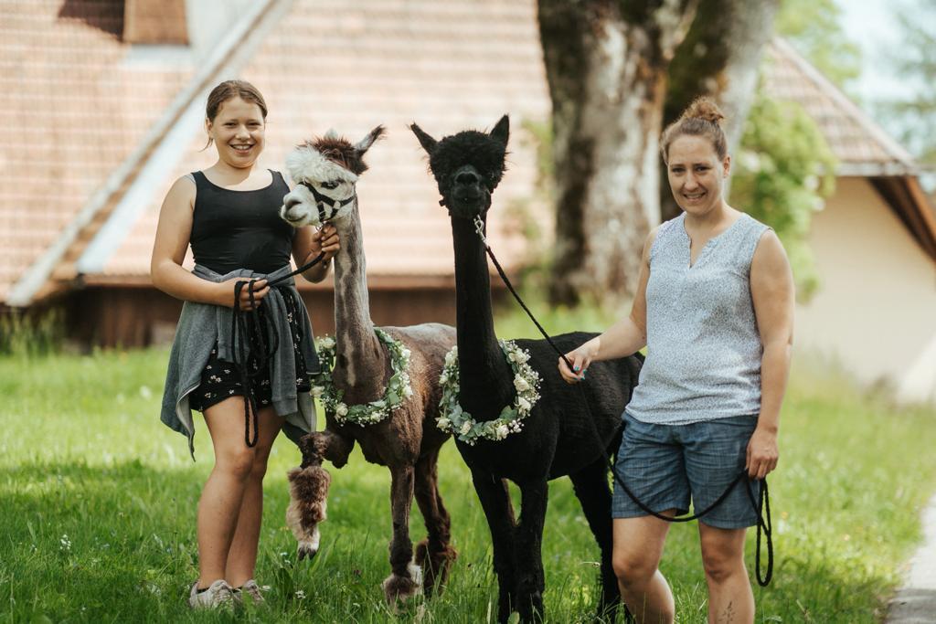 Beatrice Freter mit Ihrer Tochter und einem braunen und schwarzen Alpaka
