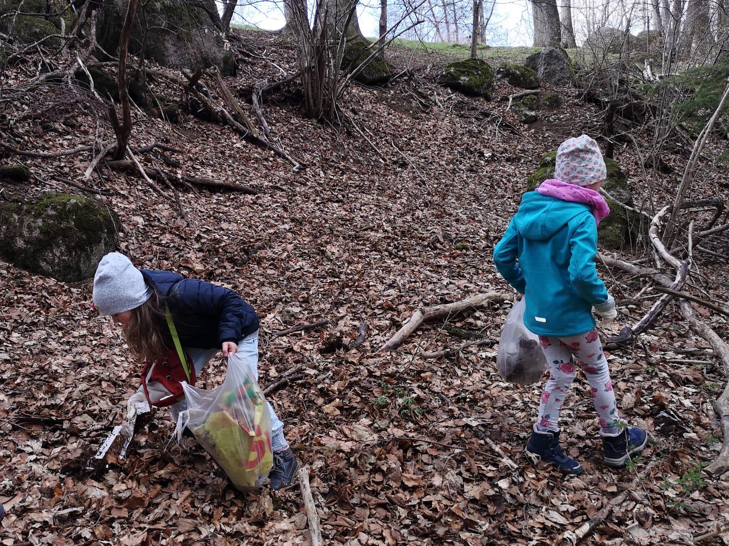 Kinder, die im Wald den Müll aufsammeln