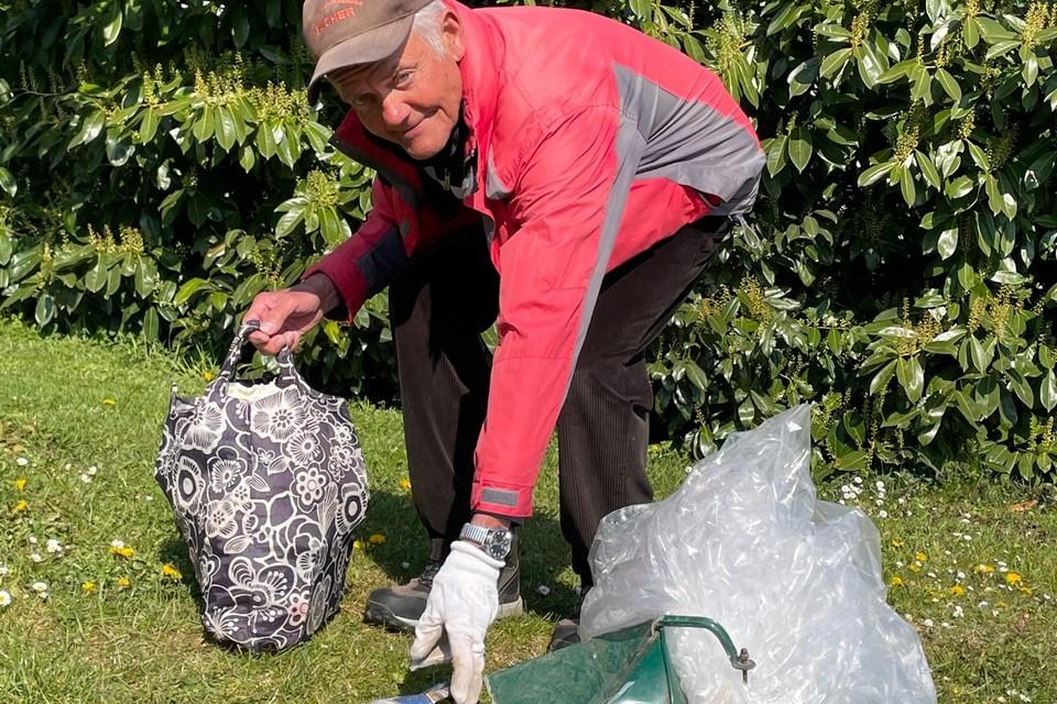 Ein Herr sammelt Müll auf